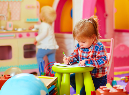 active kids: cute little girl drawing with pencil in kindergarten Stock Photo