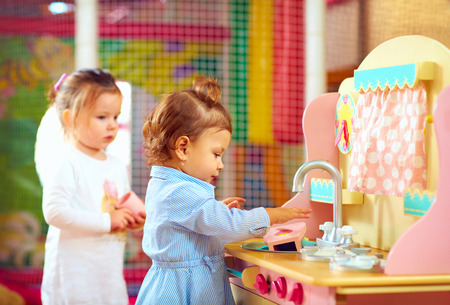 kinder: ni�as jugando en la cocina de juguete en el jard�n de infantes Foto de archivo