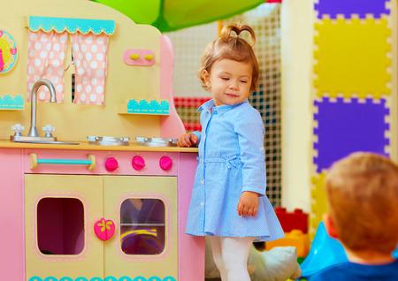 toy: little hostess at toy kitchen in kindergarten