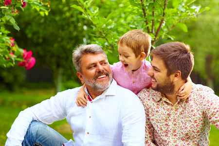 men talking: portrait of happy grandpa, father and son in spring garden