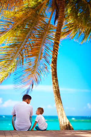 caribbean beach: happy father and son sitting near the sea during summer vacation