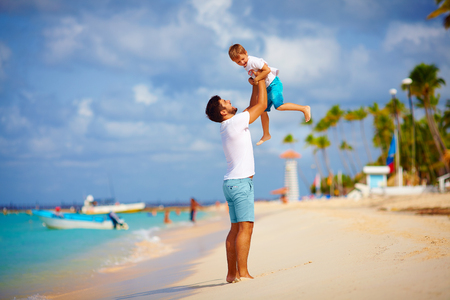 playful: playful father and son having fun on tropical beach