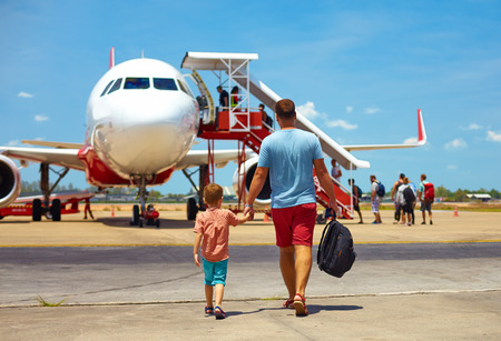 flucht: Familie zu Fuß zum Einsteigen am Flugzeug im Flughafen, Sommerurlaub