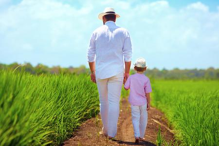 쌀 필드를 통해 걷고 맨발로 아버지와 아들