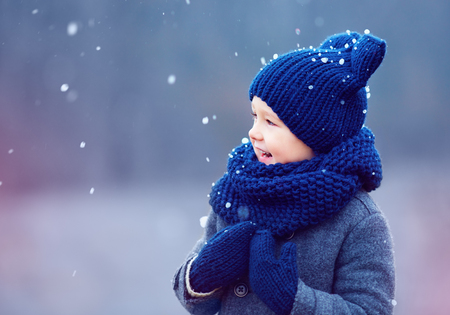wools: cute kid, boy in winter clothes playing under the snow Stock Photo