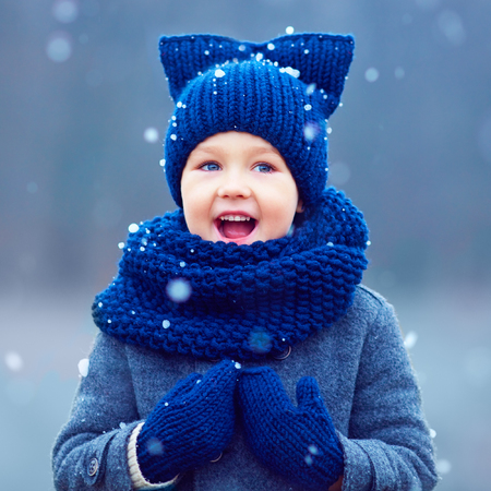 cute kid, boy in winter clothes playing under the snow Stock Photo
