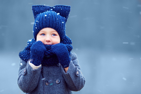 cold: cute little boy, kid in winter clothes walking under the snow