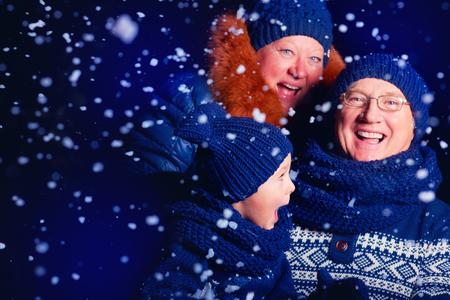 grandparent: smiling grandparent and grandson having fun under the snow
