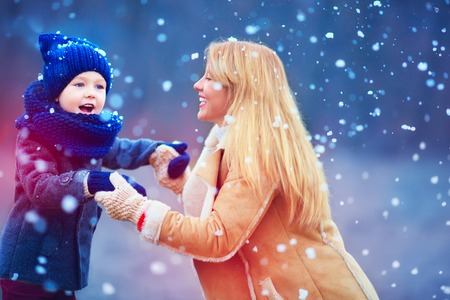 happy mother and son having fun under winter snow