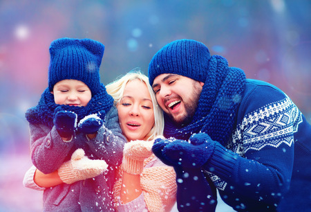 and in winter: portrait of happy family blowing winter snow Stock Photo