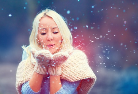 beautiful woman blowing winter snow  from knitted mittens Stock Photo