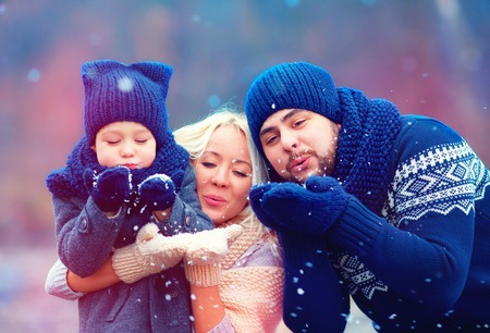 portrait of happy family blowing winter snow outdoors