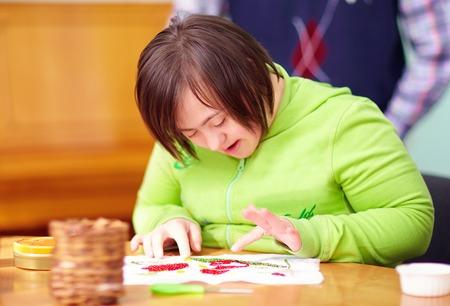 jungen erwachsenen Frau mit Behinderung in Handwerkskunst in Rehabilitationszentrum engagiert Standard-Bild