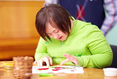 mental activity: young adult woman with disability engaged in craftsmanship in rehabilitation center
