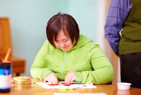 young adult woman with disability engaged in craftsmanship in rehabilitation center 版權商用圖片 - 50488419