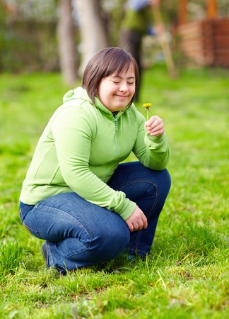 春の庭で自然を楽しんでいる障害のある若い大人の女性