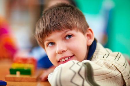 kinderen: portret van lachende jonge jongen, kind met een handicap Stockfoto