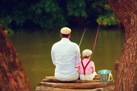 귀여운 원시 아버지와 아들이 아름다운 원시 자연 사이에 함께 낚시