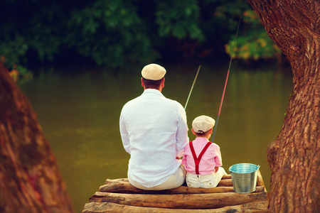 かわいい父と息子が一緒に美しい手付かずの自然の中で釣り