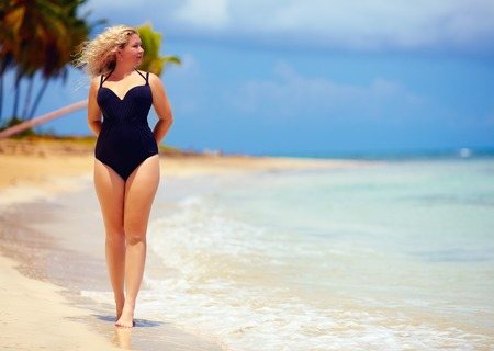 beautiful plus size woman walking on summer beach