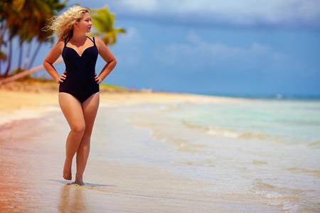 mooie plus size vrouw lopen op zomer strand