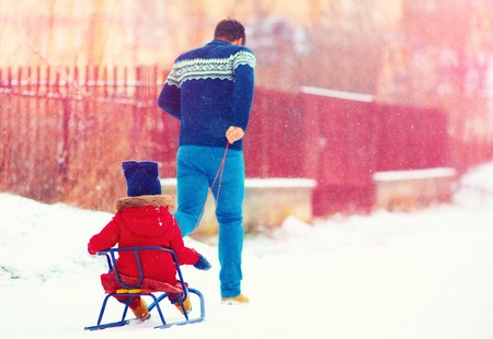 sledging people: happy father and kid having fun with sledge under winter snow