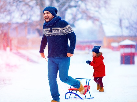 sledging people: happy father and son having fun with sledge under winter snow