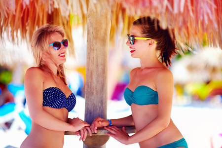 bikini pool: beautiful happy women, friends enjoy summer vacation on tropical beach Stock Photo