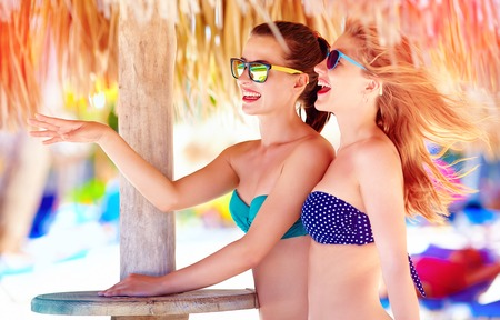 vacation summer: beautiful girls in bikini talking on tropical beach, summer vacation Stock Photo