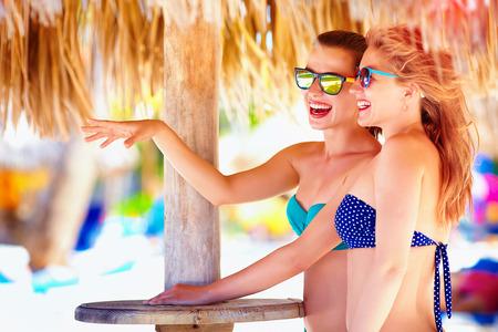 all smiles: beautiful girls in bikini talking on tropical beach, summer vacation Stock Photo