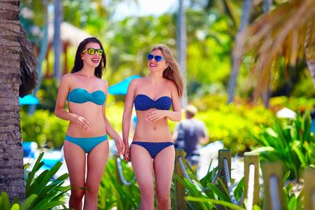 girls in bikini: happy young girls walking on tropical beach, during summer vacation