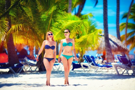 all seasons: happy young girls walking on tropical beach, during summer vacation