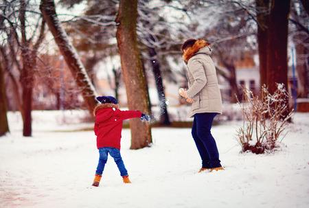 Hurl: active father and son playing snowballs in winter park