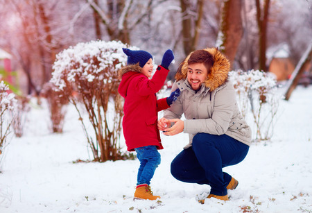 neve palle: Padre e figlio giocare a palle di neve attivi nel parco d'inverno