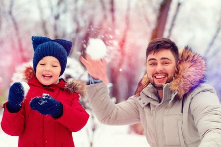 palle di neve: Padre e figlio giocare a palle di neve attivi nel parco d'inverno