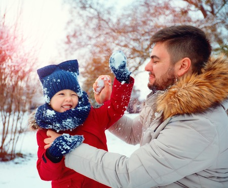 snowballs: Padre e figlio giocare a palle di neve attivi nel parco d'inverno
