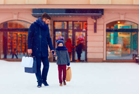 father and son on winter shopping in city, holiday season