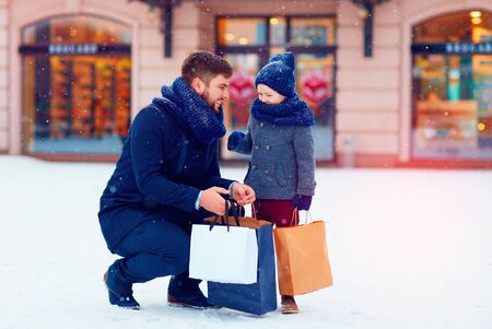father and son on winter shopping in city, holiday season, buying presents Stock Photo