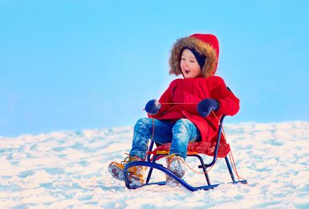 downhill: happy kid sliding downhill on winter snow