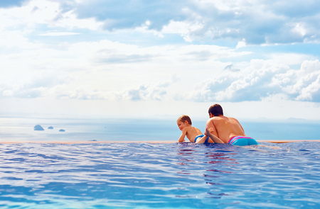 happy father and son enjoy beautiful seascape from infinity pool, vacation concept Zdjęcie Seryjne