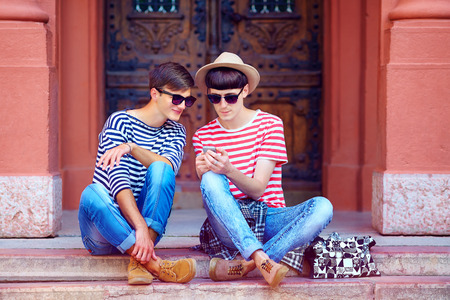 lgbt: young male couple chatting through the mobile device