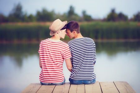 gay couple in love on river bank Stock Photo