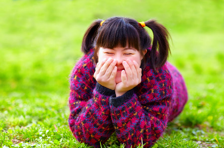 cerebral palsy: happy young girl with disability on spring lawn