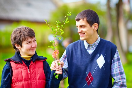 special needs: portrait of happy woman and man with disability together on spring lawn