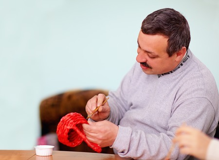 young adult man engaged in craft work in rehabilitation center