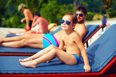 all seasons: cute young kid, boy relaxing on lounge during summer vacation
