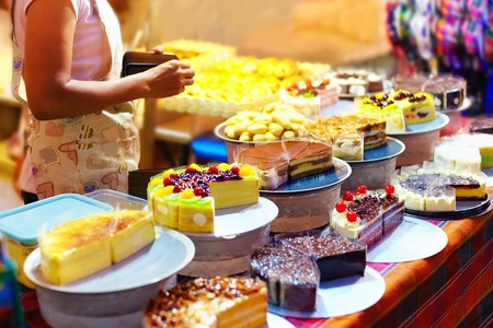 sweet tasty cakes  on display at pastry stall, at night street market Stock Photo