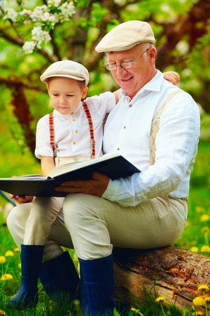 happy grandfather and grandson reading book at spring apple garden