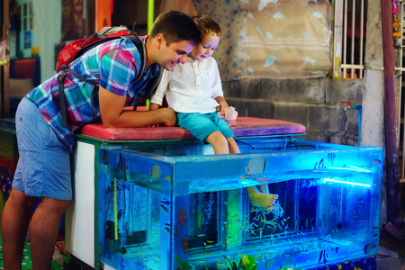 aquarium tank: happy father and son at fish pedicure treatment at street market