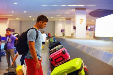 젊은 성인 남자 승객은 공항 터미널에서 수하물을 기다리고